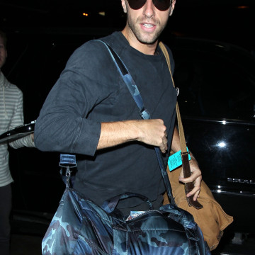 Chris Martin gives a smile and a wave after grabbing his bags at LAX